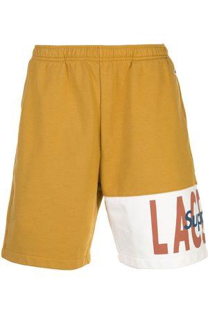 Supreme Lacoste logo panel track shorts
