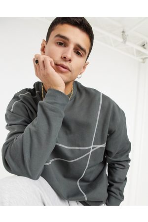 ASOS Oversized sweatshirt in washed black with contrast flat lock stitching