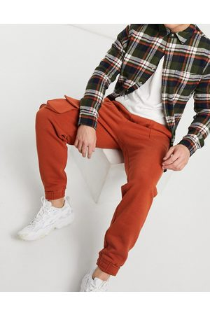 ASOS Tapered joggers with multi utility pockets & tab cuffs in burnt red
