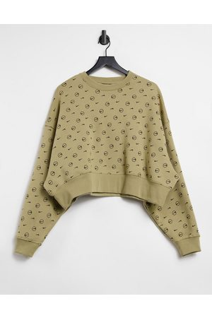 Nike All over logo print cropped sweatshirt in camel
