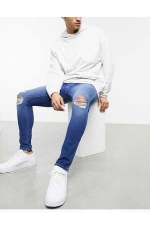 ASOS DESIGN Spray on jeans in power stretch with 'less thirsty' wash in mid with knee rips