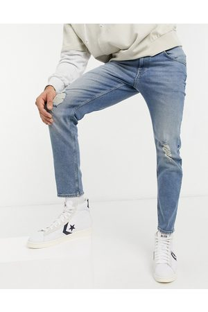 ASOS Stretch tapered jeans in mid wash with knee rips