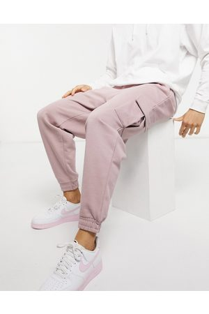 ASOS Men Sets - Co-ord oversized joggers with cargo pockets in pastel pink