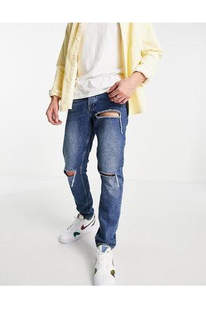 ASOS DESIGN Slim jeans in vintage dark wash with rips