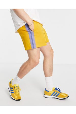 ASOS Oversized jersey shorts with pin tucks & side tape in mustard