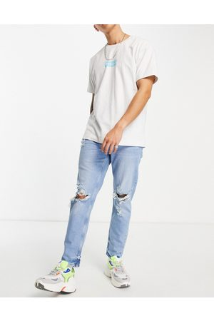 ASOS Men Tapered - Tapered carrot jeans in light wash with knee rips