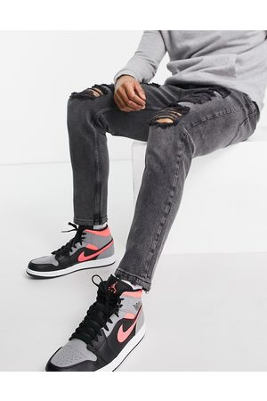 ASOS Tapered carrot jeans in washed with heavy rips