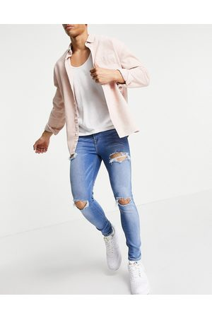 ASOS Spray on jeans with power stretch in mid wash with heavy rips