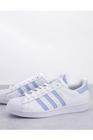 adidas Superstar trainers in with light blue stripes