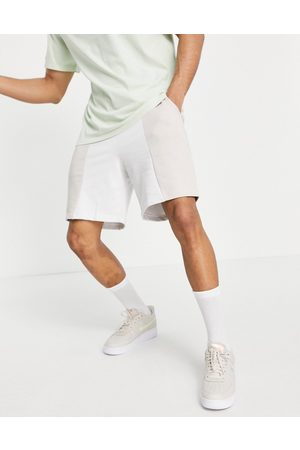 ASOS ASOS Unrvlld Spply co-ord shorts with cut and sew detailing and logo print-Neutral