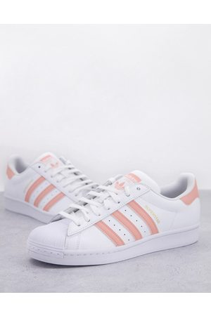 adidas Superstar trainers in with pink stripes