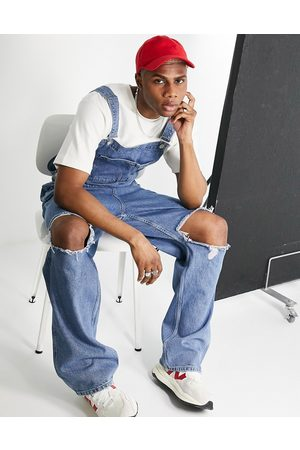ASOS Baggy denim dungarees in mid wash with knee rips