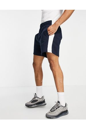 ASOS DESIGN Oversized jersey shorts with side stripe in navy