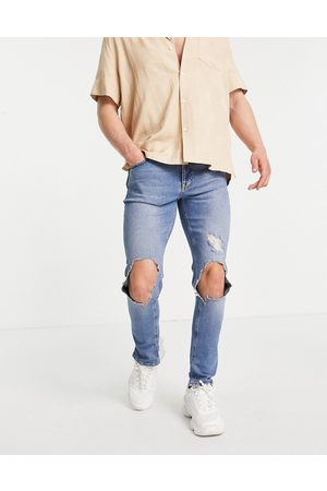ASOS DESIGN Skinny jeans with knee rips and destroyed hem in mid wash