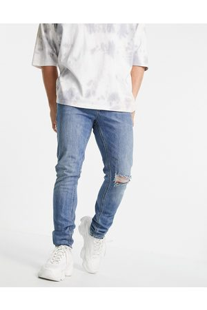 ASOS Cone Mill Denim skinny fit 'American classic' jeans in mid wash with knee rip