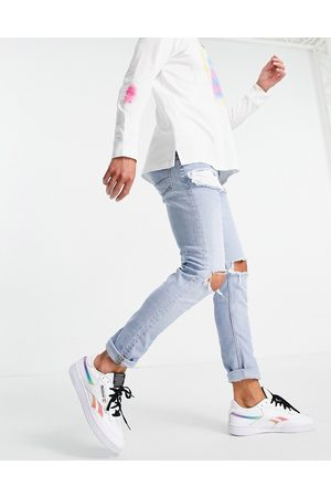 ASOS DESIGN Skinny jeans in light wash with heavy rips