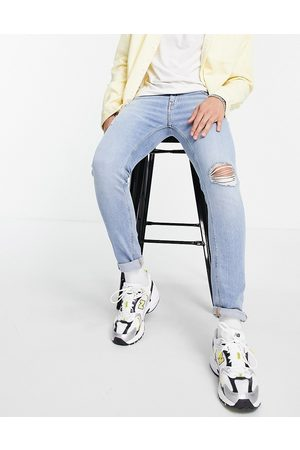 ASOS DESIGN Skinny jeans with 'less thirsty' wash in light with rips