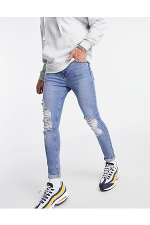 ASOS DESIGN Spray on jeans with power stretch in vintage mid wash with knee rips