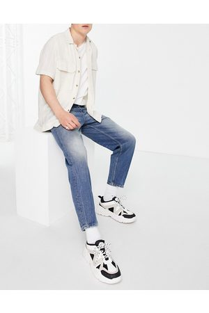 ASOS DESIGN Relaxed tapered jeans in tinted dark wash