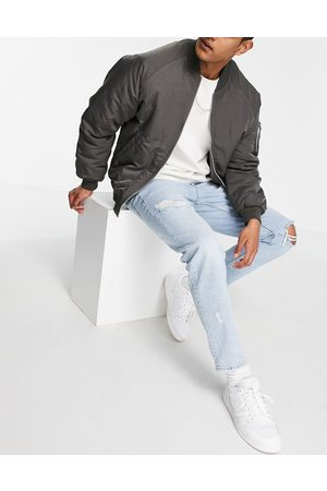 ASOS DESIGN Tapered jeans in 90's light wash with rips