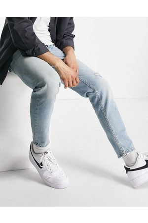 ASOS DESIGN Tapered jeans in vintage light wash with rip