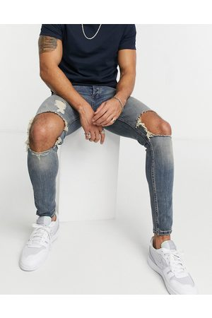 Topman Organic cotton blend spray on jeans with blowout rips in mid wash