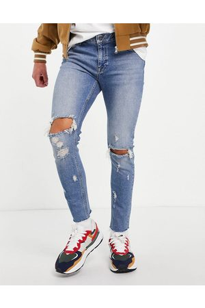 ASOS DESIGN Skinny jeans in mid wash with knee rips and raw hem
