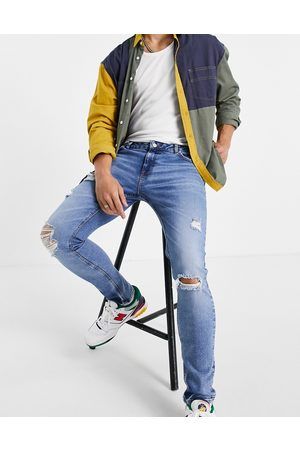 ASOS DESIGN Skinny jeans in mid wash with heavy rips