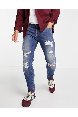 ASOS Skinny jeans in mid wash with heavy rips and raw hem
