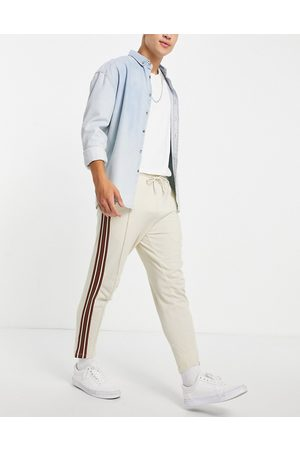 ASOS Tapered fixed hem joggers with pin tucks & side tape in -Neutral