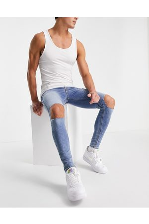 ASOS DESIGN Spray on jeans with powerstretch in mid wash with knee rips