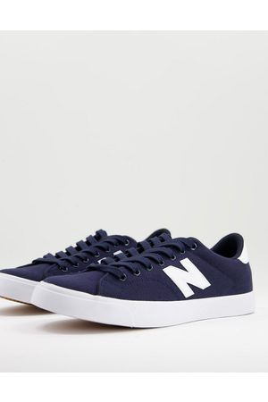 New Balance 210 court trainers in navy and white