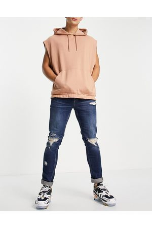 ASOS DESIGN Skinny jeans in dark wash with heavy rips