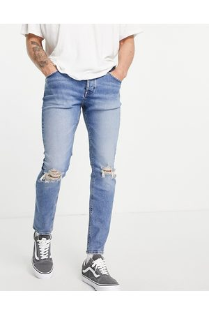 ASOS DESIGN Organic cotton blend skinny jeans in light wash with knee rip