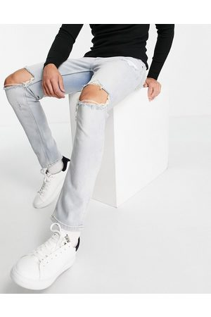 ASOS DESIGN Stretch slim jeans in vintage light wash with knee rips