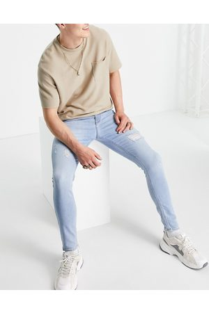 ASOS Men Skinny - Spray on jeans with power stretch in 'less thirsty' light wash with rips