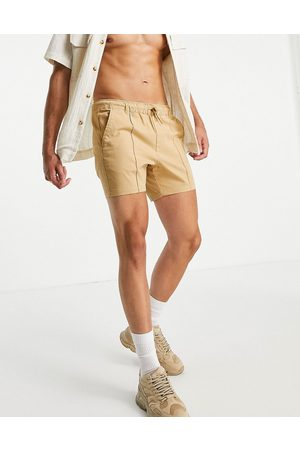 ASOS Skinny chino shorter shorts with pin tuck and elasticated waist in mustard