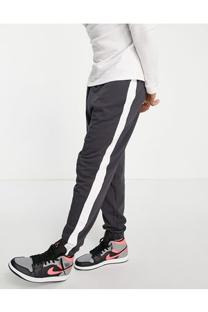 ASOS DESIGN Oversized joggers with side stripe in washed black